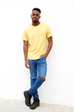 Full length portrait of cool young black man standing against white wall