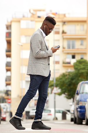 Full body side portrait of young african businessman walking in the city with mobile phone and earphones