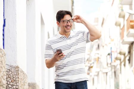행복 한 노인 휴대 전화와 함께 야외에서 산책 하 고 웃 고의 초상화