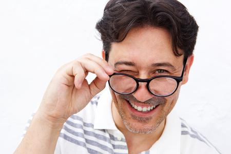 Close up of cheerful mature man holding glasses and winking Stock Photo