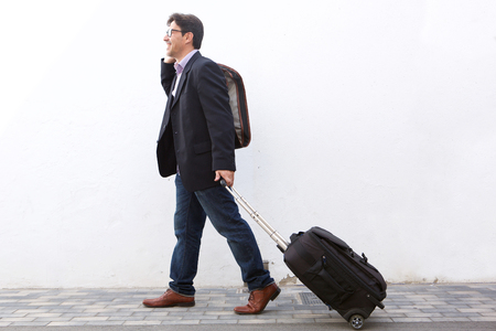 Full length side portrait of businessman traveling with his suitcase and talking on cell phone outdoors