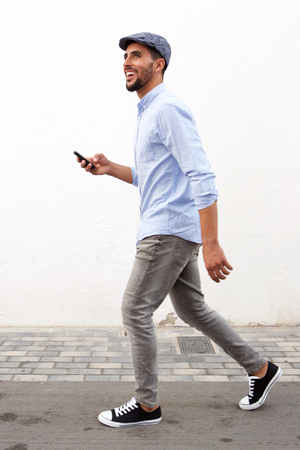 Full length side portrait of smiling man walking with cellphone against white wall Banque d'images - 94643764
