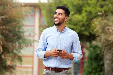 Close up portrait of smiling young arabic man walking with cellphone outside Banque d'images - 94427897