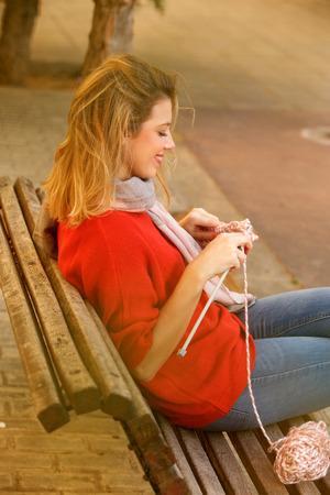 Side portrait of happy young woman sitting on bench knitting sweater
