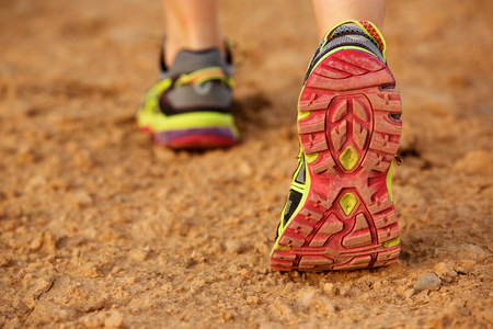 Low angle back of female shoe walking on dirt road Stock Photo