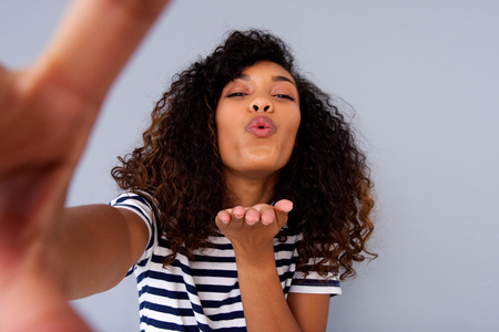 Portrait of young woman taking selfie and blowing a kiss