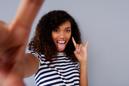 Portrait of fun young african american woman taking selfie with tongue out