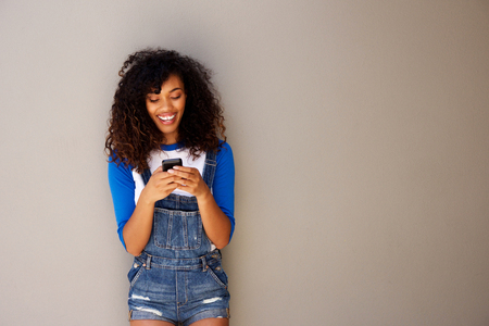 Horizontal portrait of beautiful young black woman looking at cellphone  Stock Photo