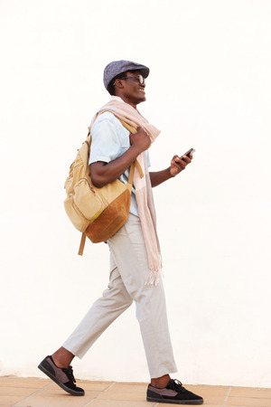 Full length side portrait of smiling African American man walking with cell phone