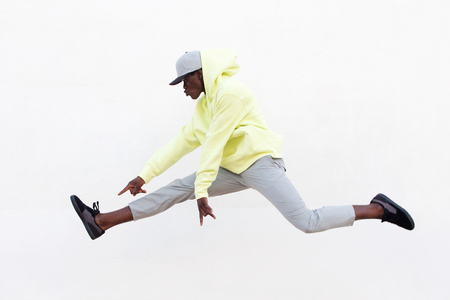 Portrait of young african man dancer doing leg split in mid air over white background