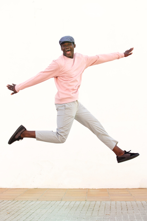 Portrait of excited young african man jumping with joy against white wall