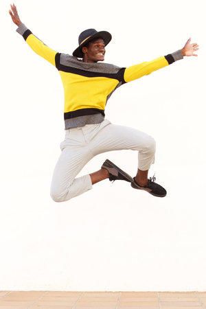 Portrait of happy young african man jumping in air over white background Фото со стока - 95800015