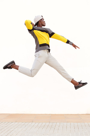Portrait of cool young african man jumping in air
