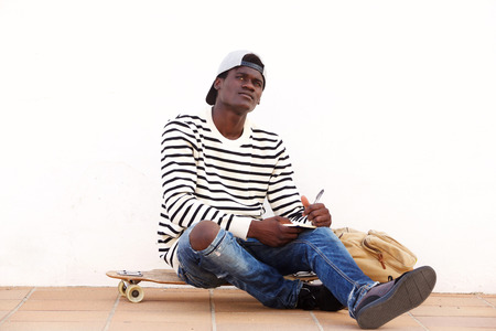 Portrait of thoughtful young african man sitting on skateboard outdoors with book