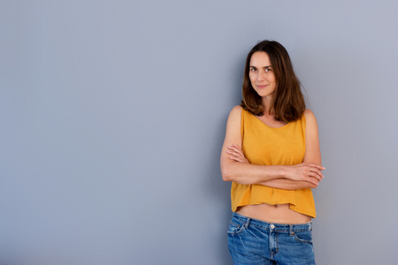 Portrait of confident older woman standing by gray wall with arms crossed