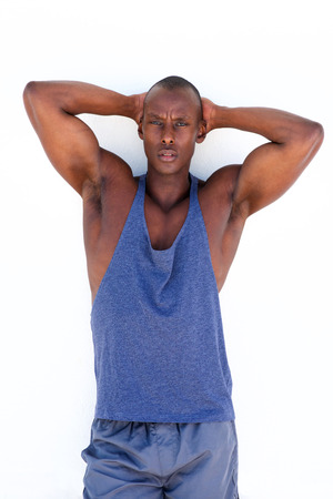 Portrait of handsome african american exercise man standing against white wall with hands behind head
