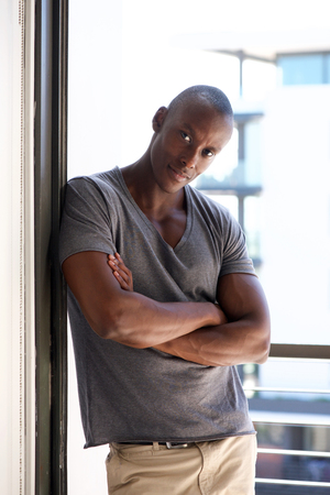 Portrait of a cool african american man leaning against wall by window Stock Photo - 96773202