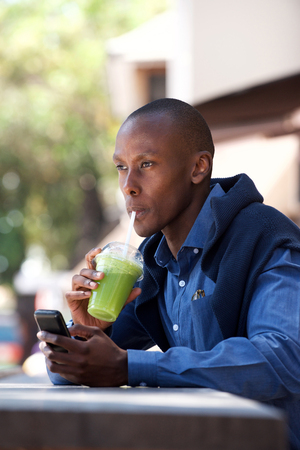 Portrait of cool black guy sitting outside with cellphone and drink