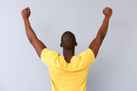 Portrait from behind of cheerful black man with arms raised