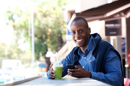 Portrait of happy african american man smiling with mobile phone and drink outside