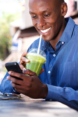 Portrait of smiling african american businessman using cellphone during lunch break Stock Photo