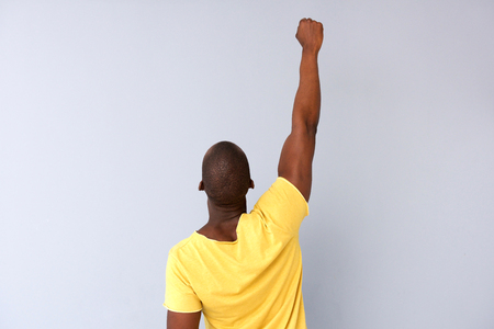 Back of a black man punching the air against gray background