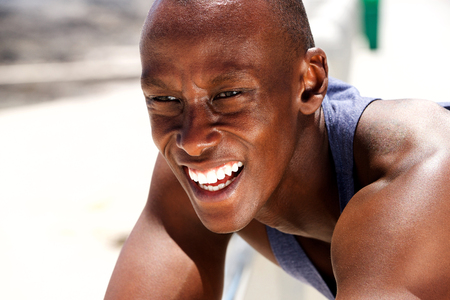 Close up portrait of smiling young black man in tank top