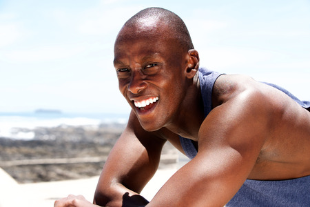 Close up portrait of happy young black man smiling in summer