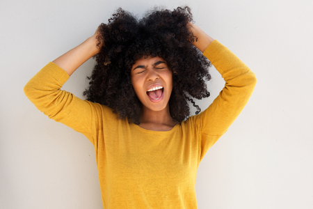 若いアフリカの女の子の叫び声と白い背景に対して彼女の髪を引っ張るの肖像画をクローズアップ