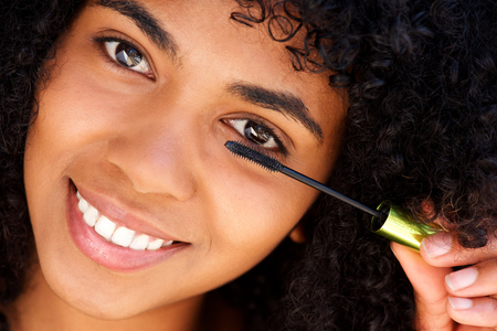 Close up portrait of attractive young black woman putting make up on eye