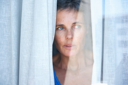 Close up portrait of older woman looking opening curtains and looking through window