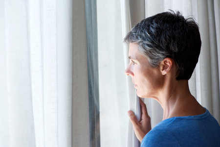 Portrait of middle age woman peeking out of window Stock Photo