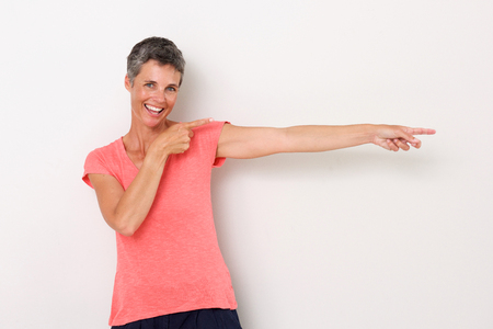 Portrait of happy woman smiling against white background and pointing fingers Stock Photo