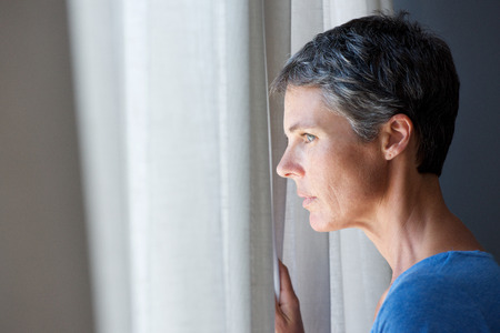 Portrait of older woman looking out window