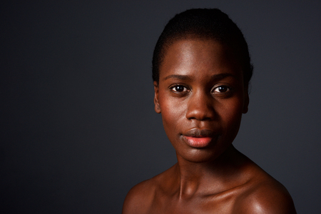 Close up portrait of beautiful african woman looking at camera with naked shoulders