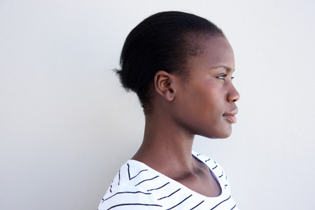 Close up profile image of young black woman against white wall 스톡 콘텐츠