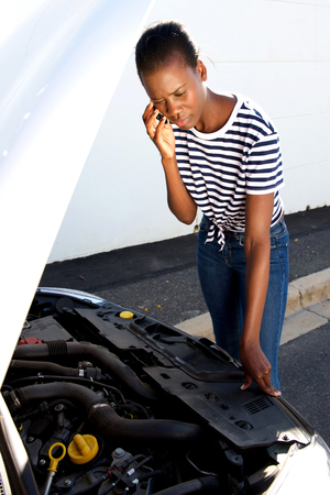 Portrait of upset young african woman standing by  broken down car parked on the side of a road and calling for assistance