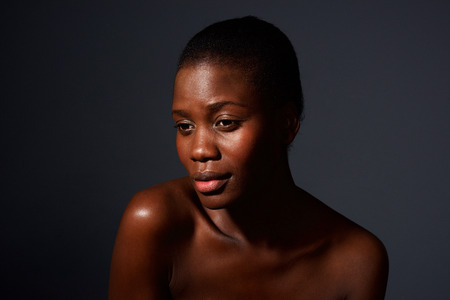 Close up portrait of attractive young african woman against gray background with naked shoulders