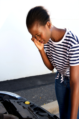 Portrait of a young african woman having trouble with her broken car calling for help on cell phone Stock Photo