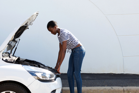 Side portrait of young african american woman looking under the hood of broken down car