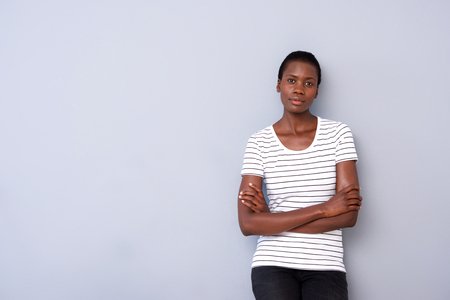 Horizontal portrait of african american woman standing with arms crossed on gray background Stock fotó