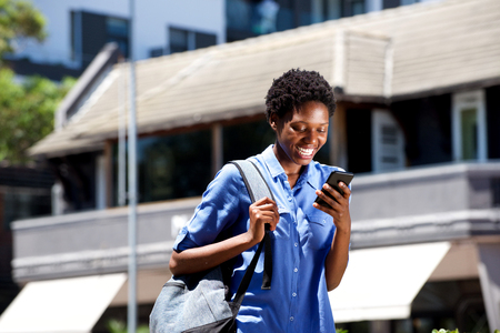 Portrait of smiling young female student walking outdoors and reading text message on smart phone