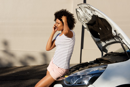 Side portrait of young woman standing by broken down car and making phone call for assistance