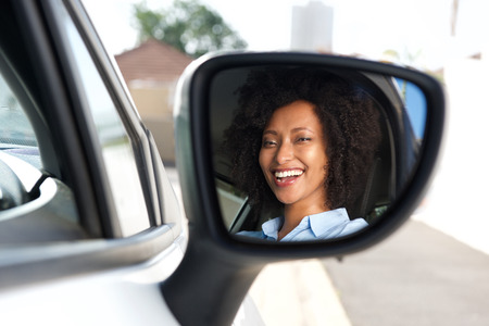 Portrait of reflection in side mirror of smiling african woman driving car