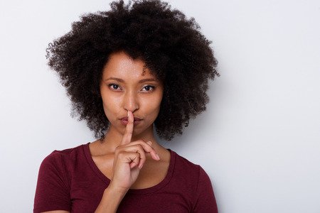 Close up portrait of beautiful young black woman with finger over lips gesturing silence