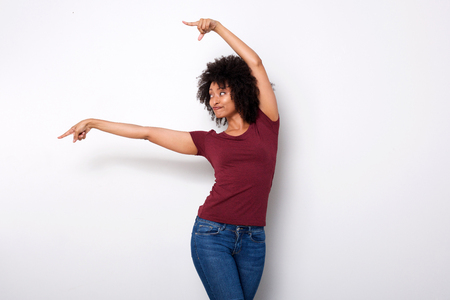Portrait of happy young african american woman pointing at side with both hands on white background Фото со стока