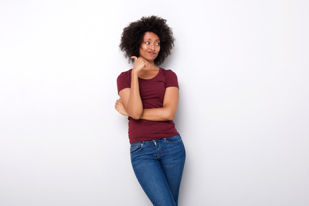 Portrait of upset young african woman pointing backwards with her thumb on white background Stock Photo
