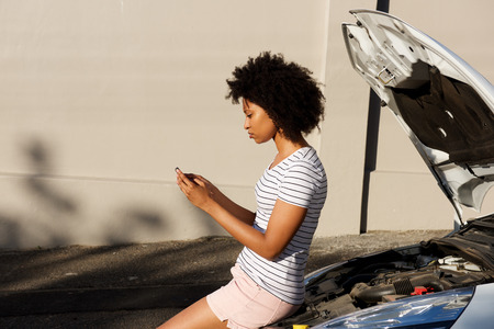 Side portrait of young black woman standing by broken down car and using cell phone for assistance
