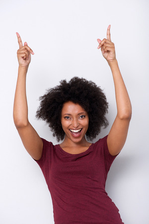 Portrait of excited young african american woman pointing up on white background 写真素材