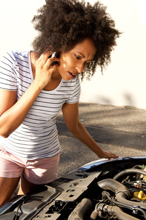 Portrait of african woman looking at her broken car and making phone call for assistance